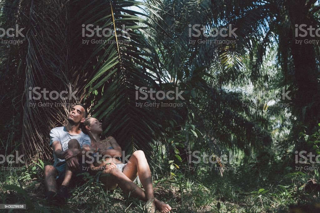 Couple resting on park trail and hugging each other stock photo
