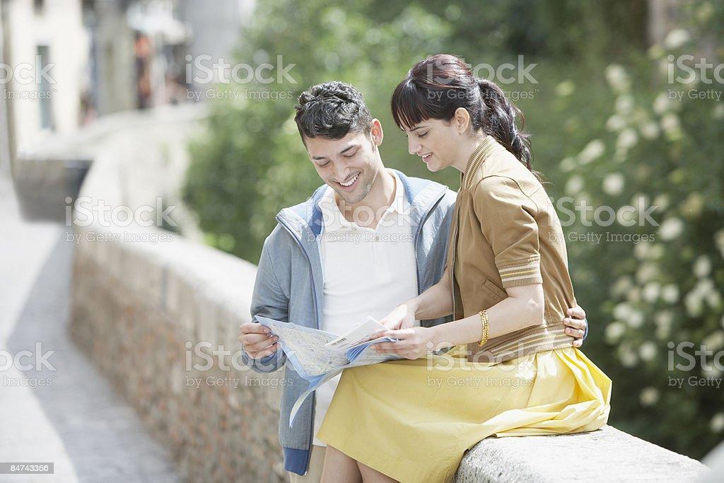 Couple reposant sur un mur et de lecture de carte photo libre de droits