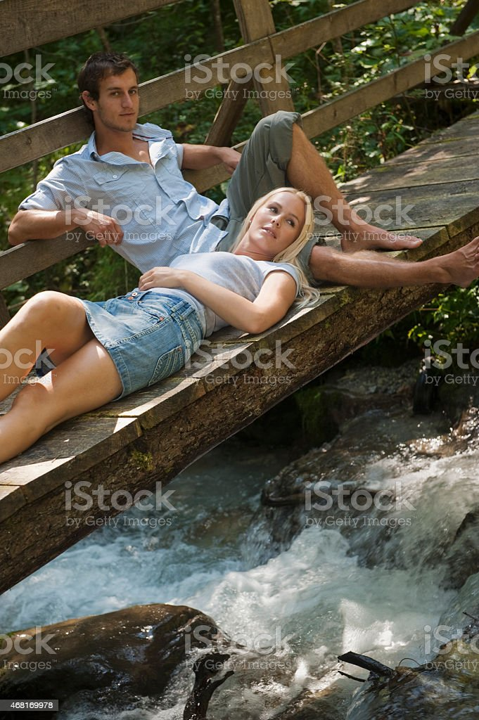 Couple resting on wooden bridge over stream stock photo