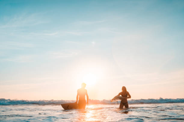 Couple returning after a long day surfing. stock photo