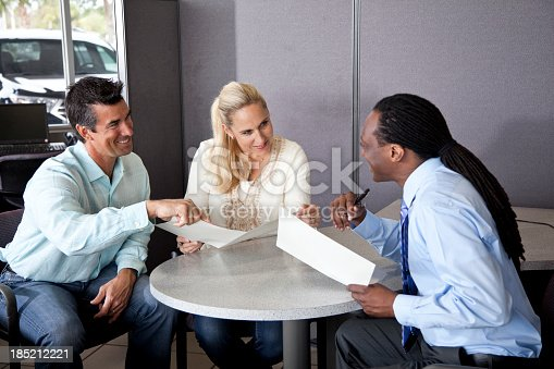 istock Couple review paperwork with car salesman 185212221