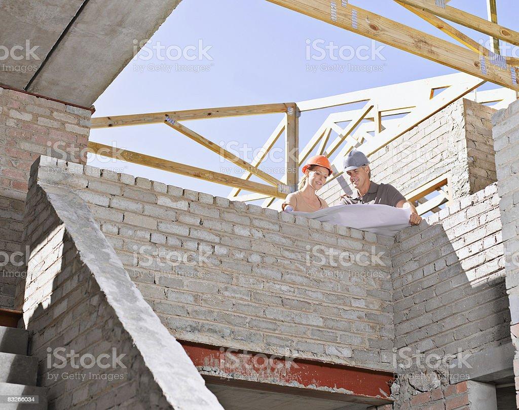 Coppia revisione di progetto in Cantiere di costruzione foto stock royalty-free