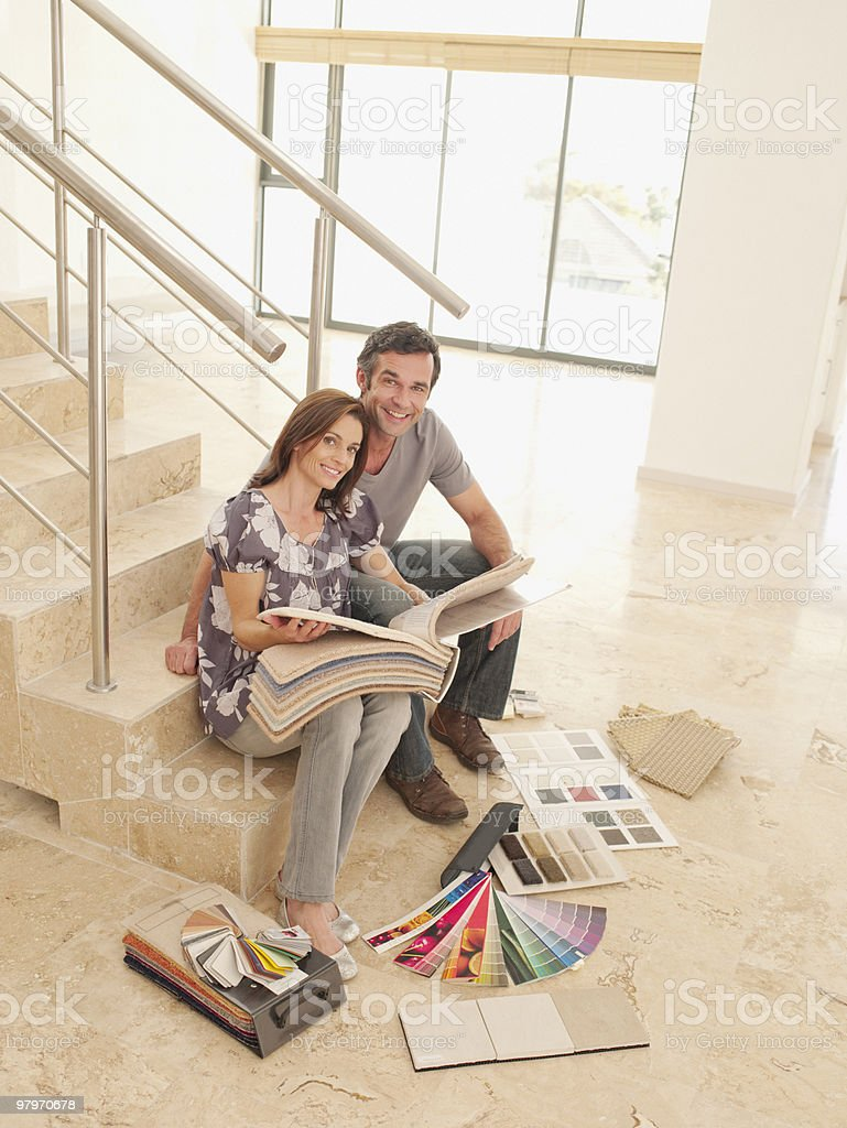 Couple reviewing carpet samples on stair in empty house royalty-free stock photo