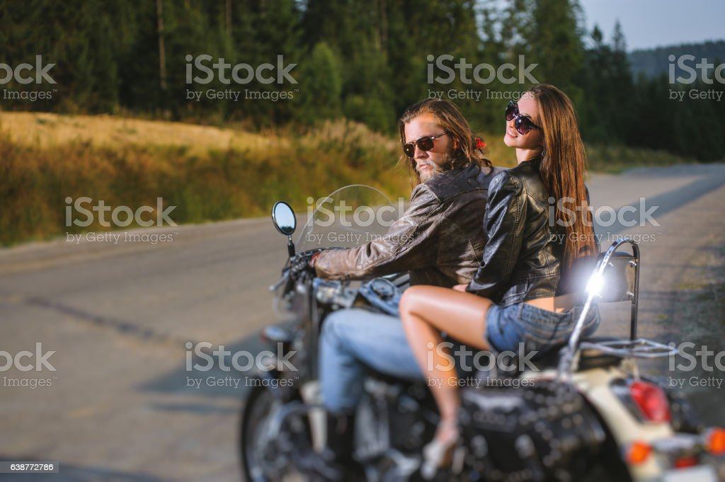 Couple riders sitting together on shiny custom made cruiser motorcycle stock photo