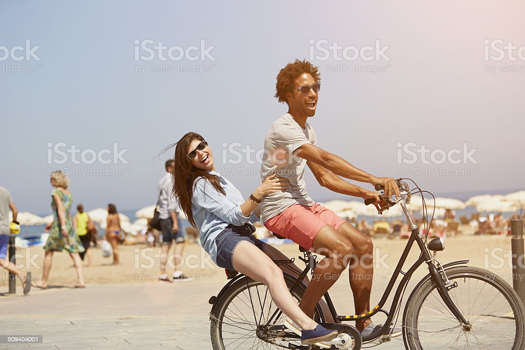 Couple riding bicycle at beach stock photo