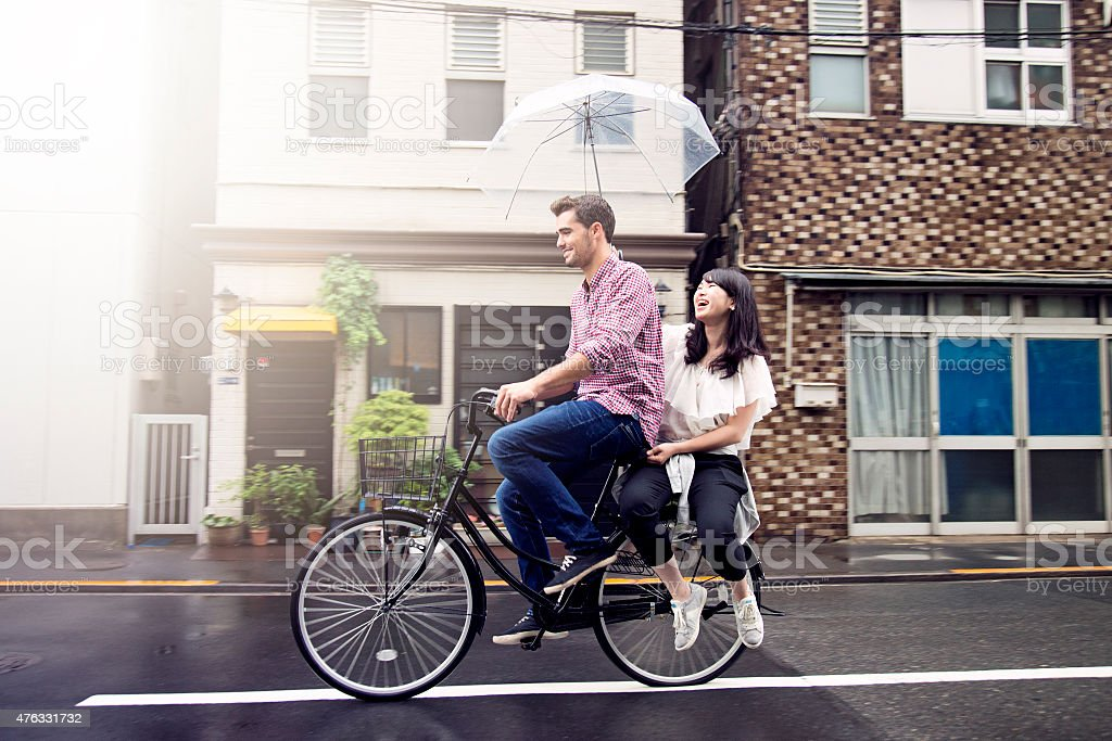 Couple Riding Bicycle on Rainy Day in Tokyo stock photo