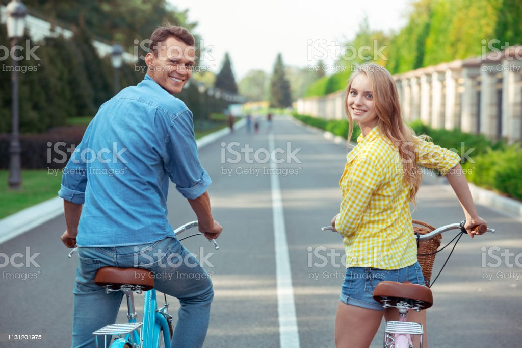 Young man and woman riding bicycle together road