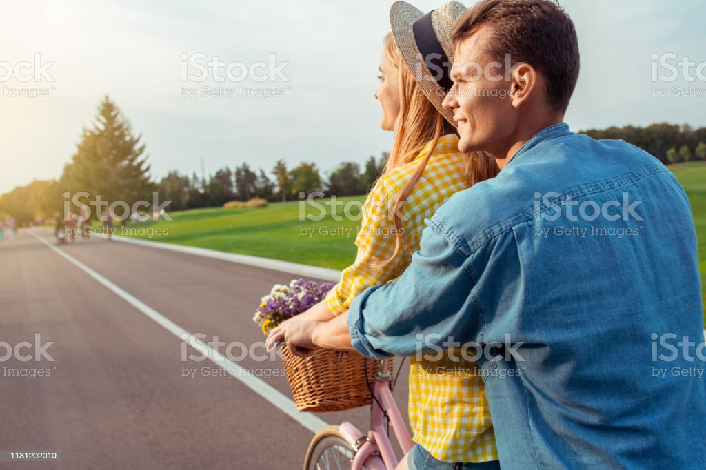 Young man and woman riding bicycle together love