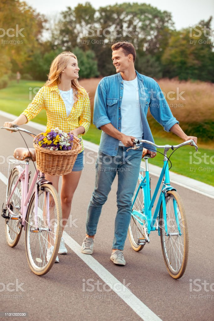 Young man and woman riding bicycle together walking