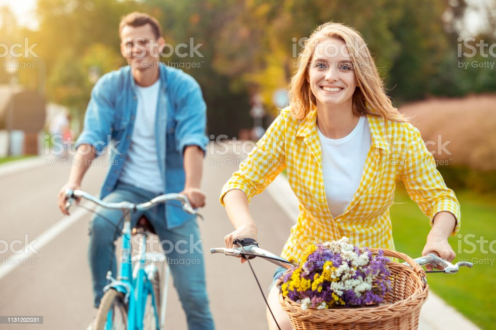 Young man and woman riding bicycle together ride