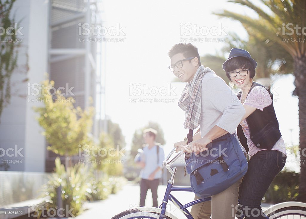 Couple riding bicycle together stock photo