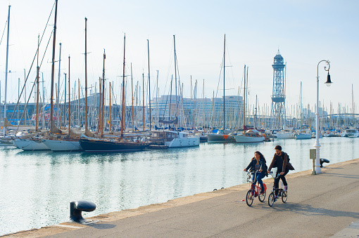 Couple riding bicycles, Barcelona marina