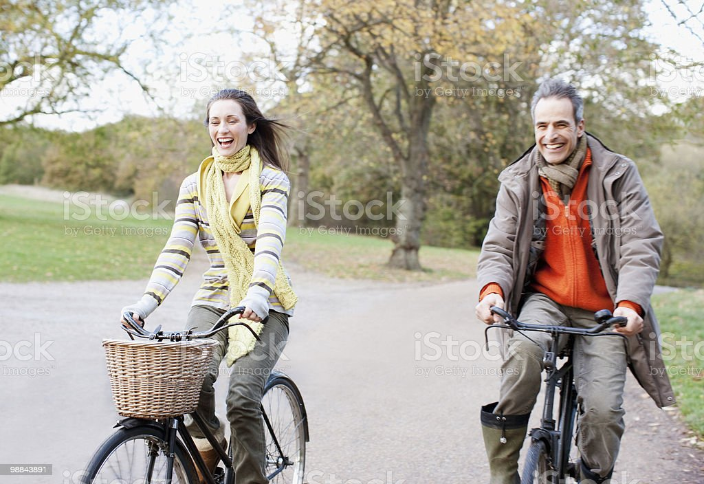 Couple riding bicycles in park royalty free stockfoto