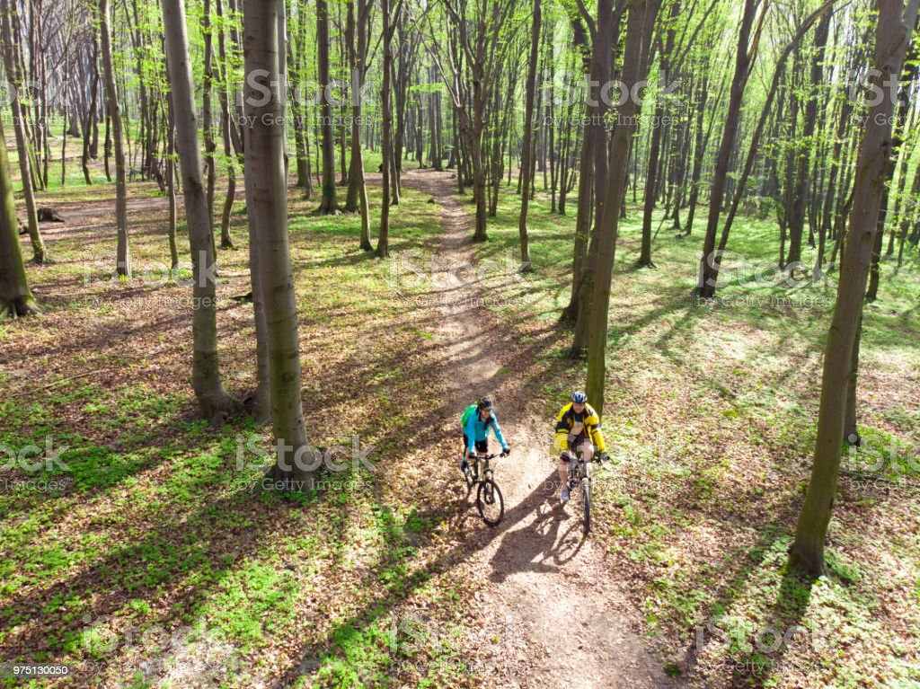 couple riding bicycles in the forest. healthy lifestyle. stock photo