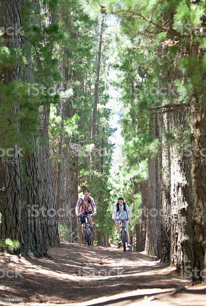Couple riding bicycles in woods royalty-free stock photo