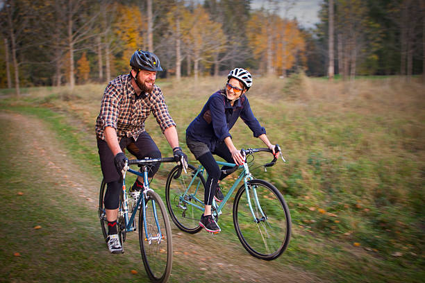 Couple riding bicycles on a cyclcocross course stock photo
