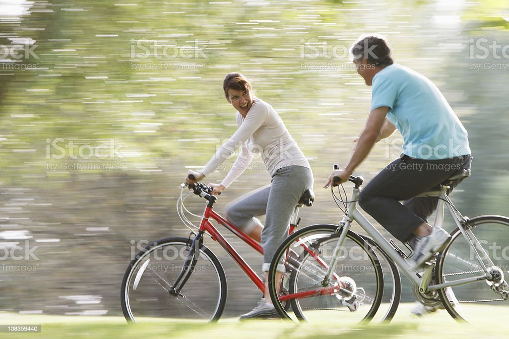 Couple riding bicycles together stock photo
