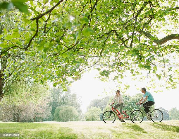 Couple riding bicycles underneath tree picture id108359509?b=1&k=6&m=108359509&s=612x612&h=fpb0pp 2qa9bids0t3la cbfecccomrq  ljxdendki=