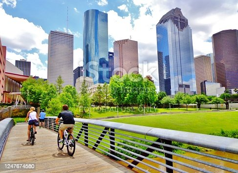 Young Man and Woman Riding Bikes on Small Wooden Bridge in Houston's Buffalo Bayou Park (view of river and skyline of downtown Houston) - Houston, Texas, USA