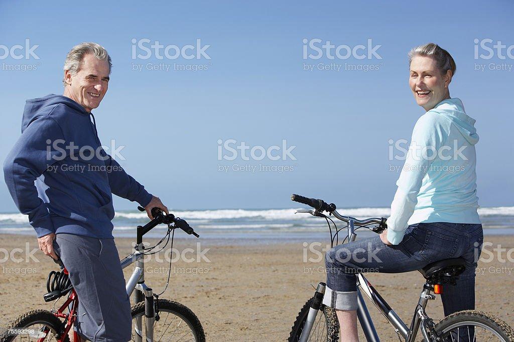 Bicicletas de equitação de casal na praia foto de stock royalty-free