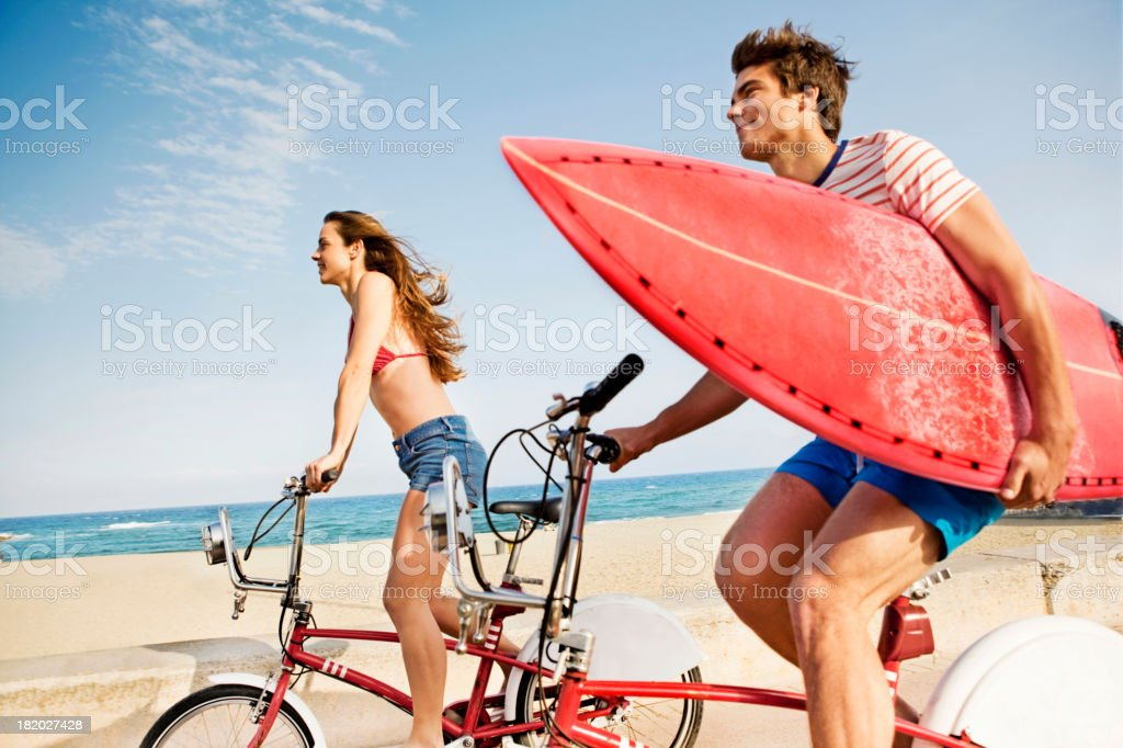 Couple riding bikes on beach boardwalk stock photo
