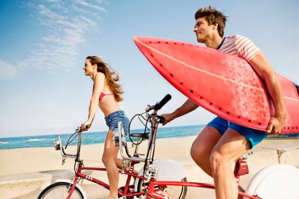 Couple riding bikes on beach boardwalk stock photo