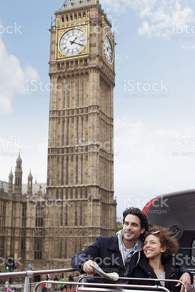 Couple riding double decker bus past Big Ben clocktower in London royalty-free stock photo