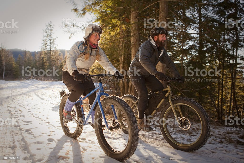 Couple riding fatbikes in the snow stock photo