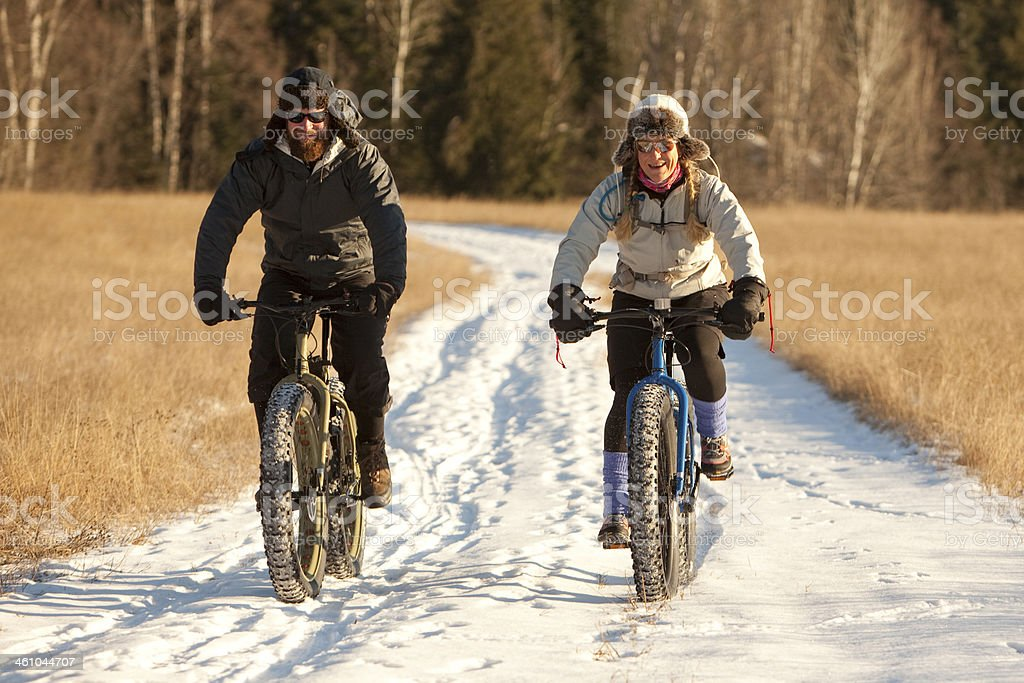 Couple riding fatbikes on a snow covered trail. stock photo