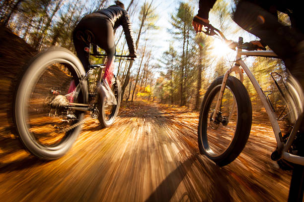 Couple riding fatbikes on trails in the fall stock photo