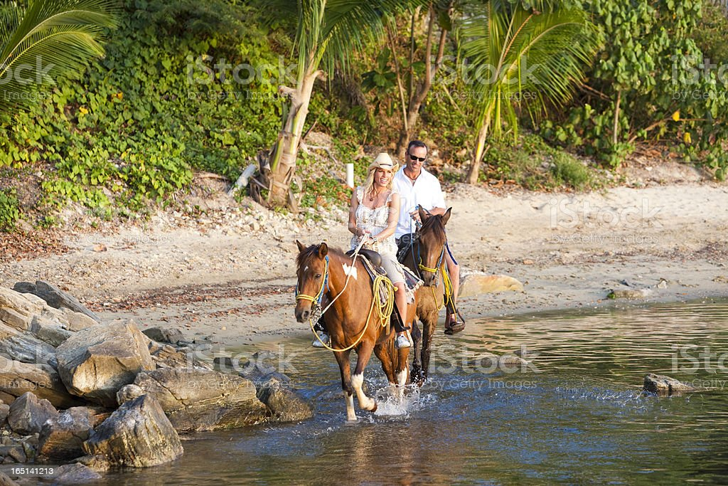 Couple riding horseback along tropical beach royalty-free stock photo