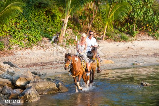 Horses splashing through Caribbean Sea while happy couple enjoys horseback ride on beach. Roatan, Honduras