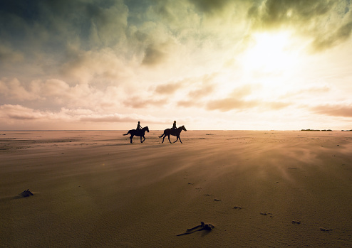 Romantic look at a silhouetted couple riding their horses across a deserted stretch of sand on a winter's afternoon. Ample copy space on clouds and sand.