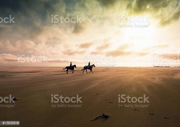 Couple riding horses across deserted sands at sunset picture id612020316?b=1&k=6&m=612020316&s=612x612&h=bgf8n cuj3mufuqxiro10a3d3lkm0vknze35c4 hare=