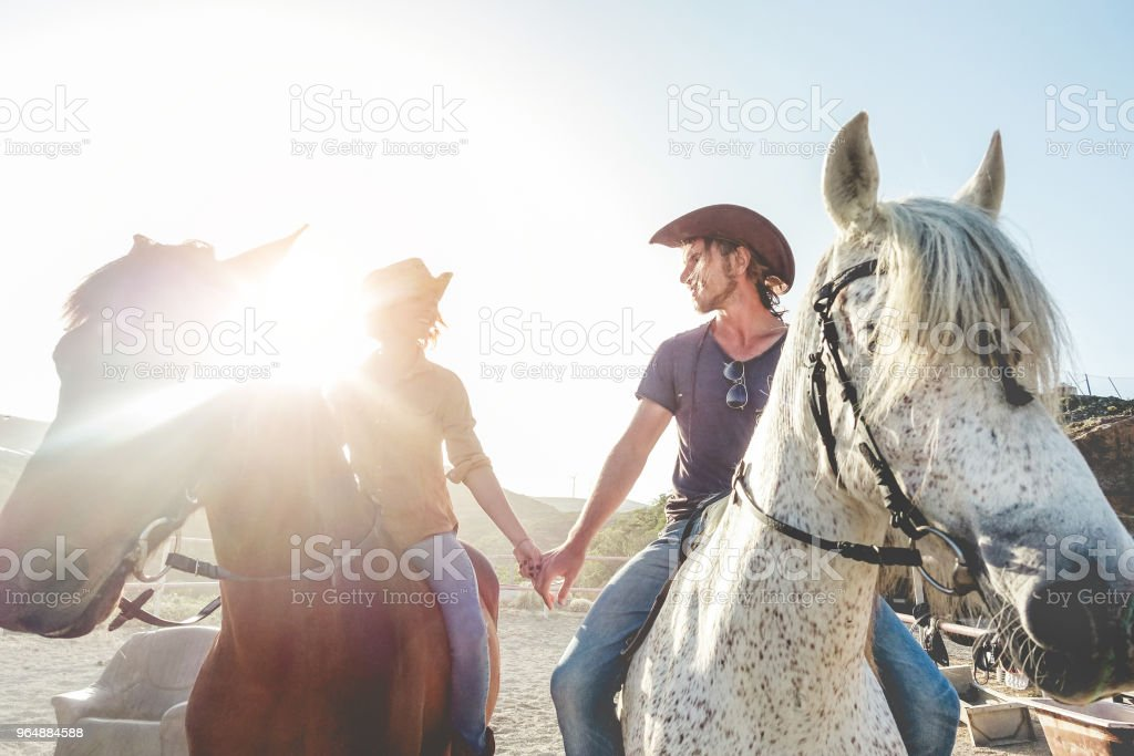 Couple riding horses during sunny day - Happy lovers having fun on summer spring vacation - Alternative holidays and love between people and animals concept - Focus on faces royalty-free stock photo