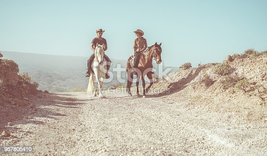 Couple riding horses in countryside nature tour - Happy people having fun on summer day - Vacation, excursion, healthy lifestyle, sport, love between people and animals concept - Focus on man face