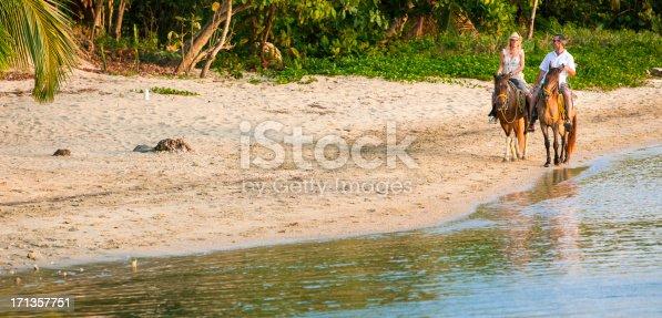 istock Couple riding horses on beach 171357751