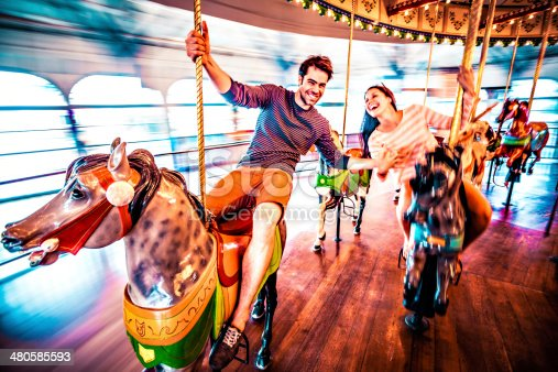 Couple in love riding horses on carousel, LA