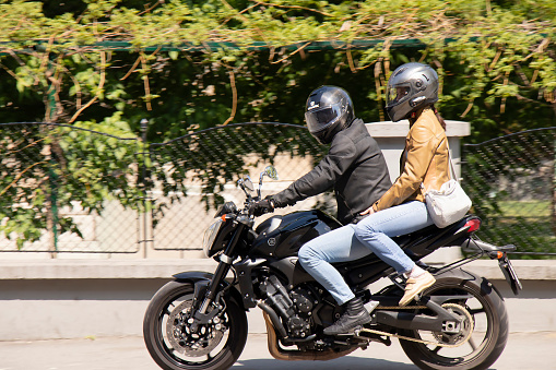 Belgrade, Serbia - April 24, 2020: Young couple riding on a motorbike a city sidewalk