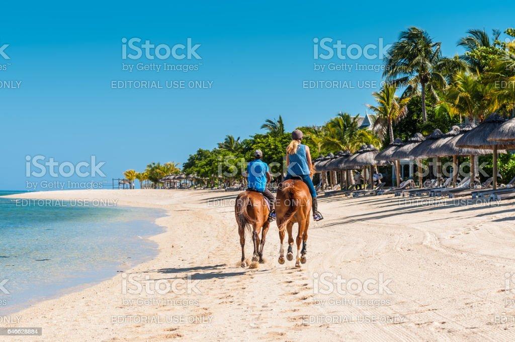 Couple riding on horseback along the sea – zdjęcie