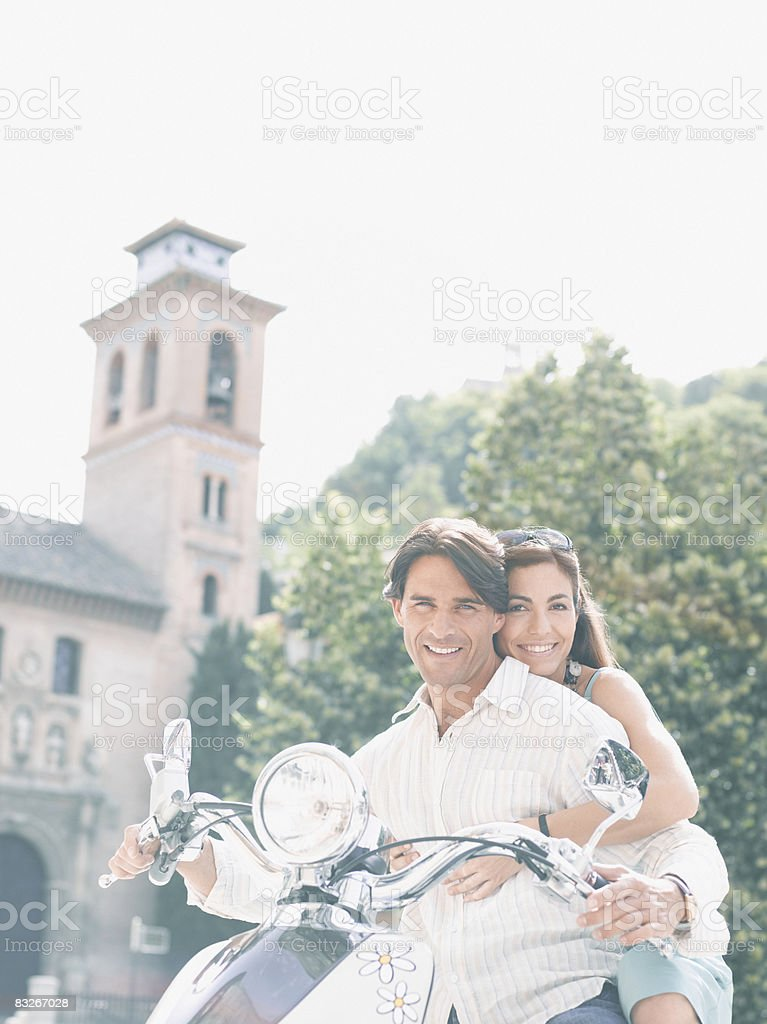 Couple riding scooter royalty free stockfoto