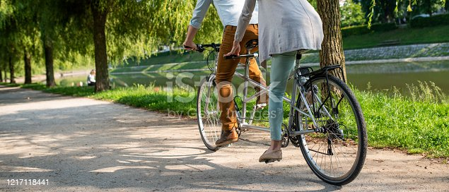 Low section of mature couple riding tandem bicycle in park.