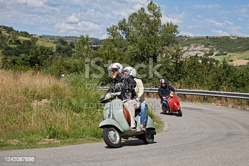 Couple riding vintage scooter Vespa in the italian hills during the meeting Raduno Vespa e Lambretta, on June 21, 2015 in Forlimpopoli, FC, Emilia-Romagna, Italy