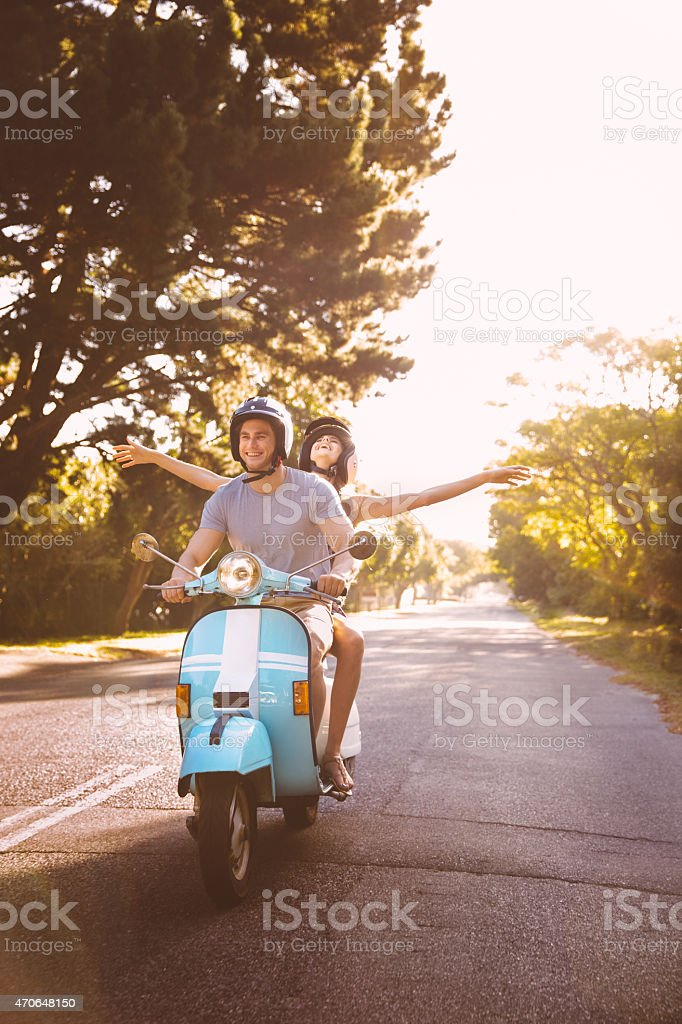 Couple road tripping on their scooter feeling free stock photo