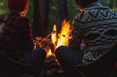 A young couple roasting marshmallows to make smores while camping.