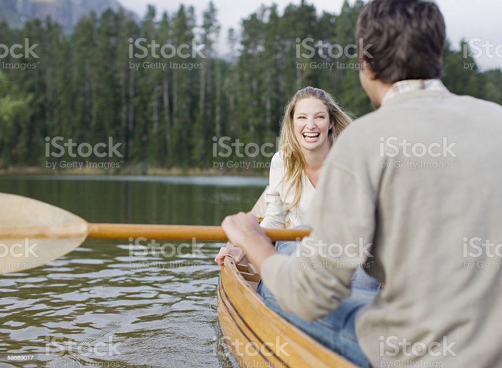 Couple rowing canoe on lake royalty-free stock photo