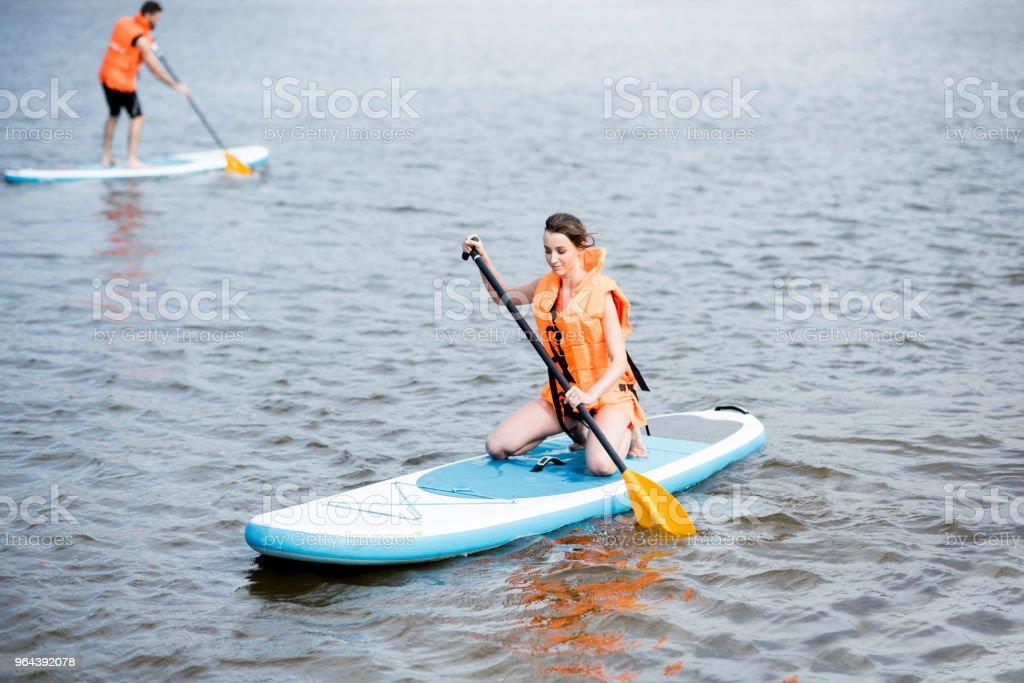 Roeien op de stand-up paddleboard paar - Royalty-free Alleen volwassenen Stockfoto