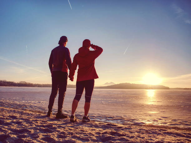 Couple runners running in winter nature. Frozen river stock photo