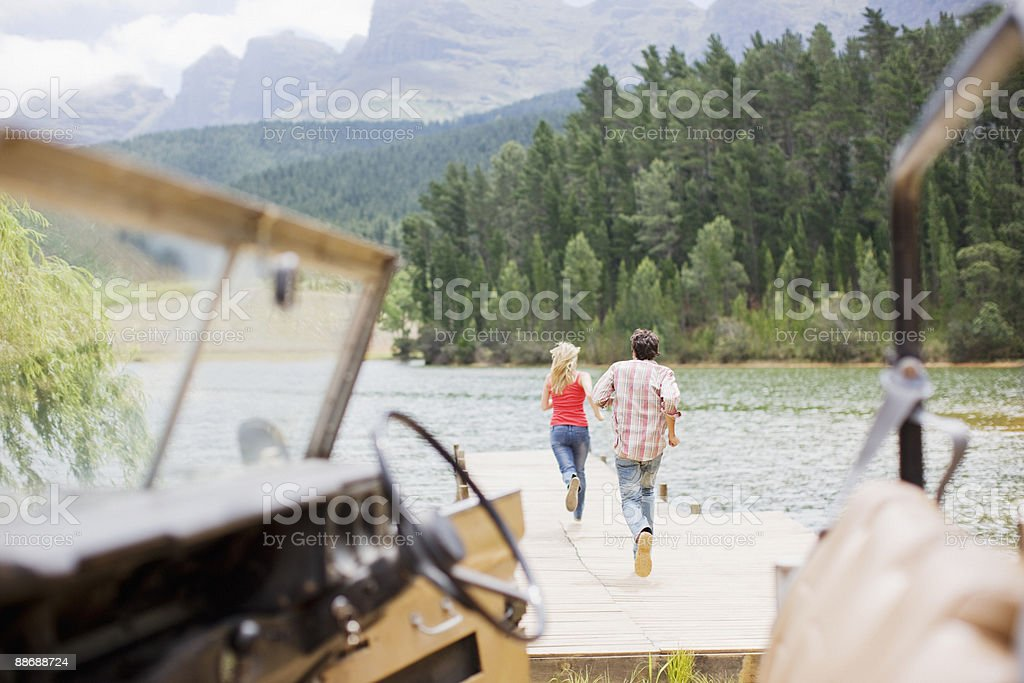 Couple running along pier at lake royalty-free stock photo