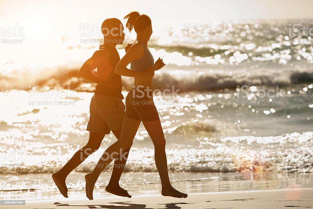 Couple running along the beach at sunset stock photo